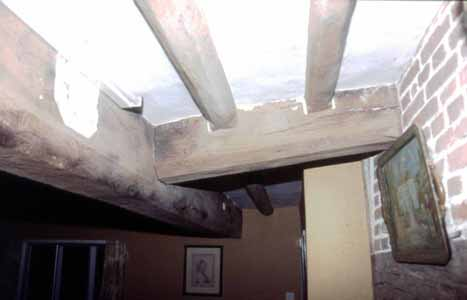 Illus. 6 The 16th century inserted hall ceiling. The plaster-filled mortise to the extreme left housed a joist that framed the demolished 16th century chimney.